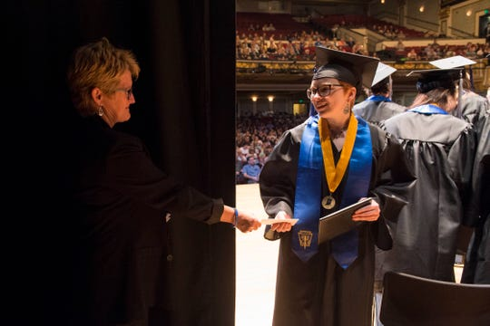 Ms. Simpkins, Left, hands Annika Roberts, right, a letter from behind the curtain after she receives her diploma during the 2019 Signature School commencement ceremony Thursday, May 23, 2019.