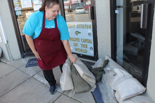 Loria Hofer, store manager at Port Clinton's Great Lakes Popcorn Company, moves around some sandbags placed by the store's front door on Madison Street Thursday. Port Clinton businesses on Madison and Jefferson Street have been hit especially hard by flooding this year, due to Lake Erie's record water levels and northeasterly winds that pushed water into the downtown area.