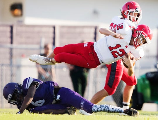 North Fort Myers High School's Aaron Cole leaps over Cypress Lake's Cedric Thomas during play on Thursday at Cypress Lake in south Fort Myers. North beat Cypress 23-21.