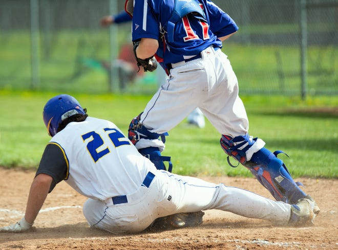 Oconto's Andrew Ramage beats the tag and slides into home to score a run in the third inning against Northland Pines on Thursday, May 23.