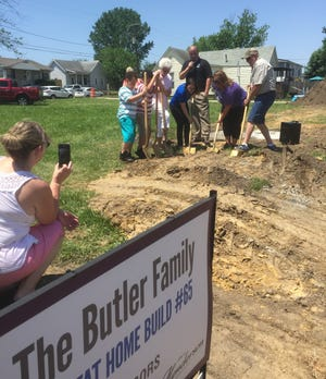 Crystal Butler, in purple shirt, breaks ground Friday afternoon on her new home on Letcher Street. Joining her are her two sons, her grandmother Gladys Butler, as well as Britney Smith, Matt Reynolds and Larry McDowell of Habitat for Humanity of Henderson.