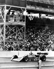 A.J. Foyt raised his hand in victory as he crossed the finish line in his Gilmore Racing Team Coyote/Foyt at the Indy 500 in 1977. He became the first man to win the race four times.