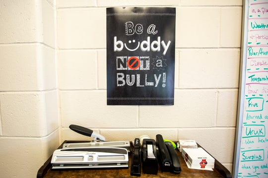 """A poster that reads, """"Be a buddy not a bully,"""" hangs on a wall, Wednesday, May 22, 2019, at City High School in Iowa City, Iowa."""