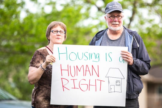 "Iowa City Councilor Pauline Taylor, left, and Charlie Eastham, of Iowa City, hold a sign that reads, ""Housing is a human right,"" while Golfview Mobile Home Court residents and community members hold a press conference following a 'town hall' with Havenpark Capitol representatives, Thursday, May 23, 2019, in North Liberty, Iowa. Eastham is a board member at the Center for Workers Justice."