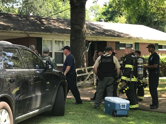 Law enforcement officers and firefighters gather outside a Humboldt home where Kenneth Price, wanted on state and federal charges, was taken into custody Friday morning.