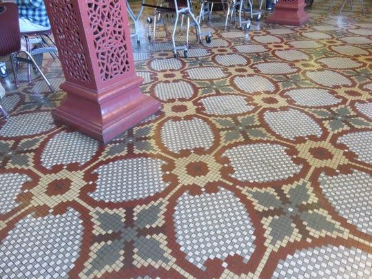 Persian rug-like tile work inside former L&N passenger station runs up to ornate metal column.
