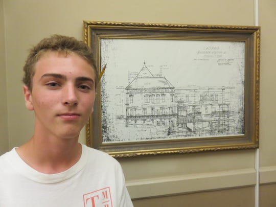 Jack Lathrop stands next to historic drawing of L&N passenger station.