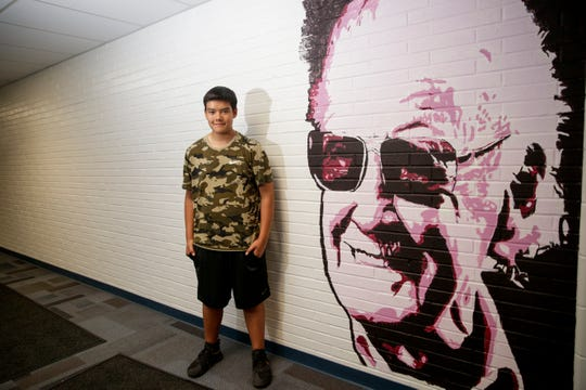 Jared Juarez poses for a photo next to a mural of Stan Lee he painted, Friday, May 24, 2019, at Wainwright Middle School in Lafayette.