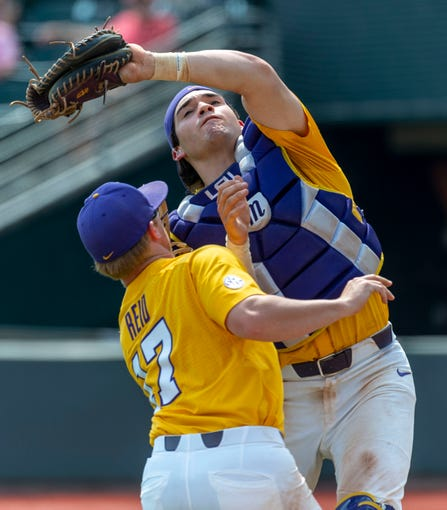 LSU infielder Chris Reid (17) and LSU catcher Saul Garza (13) collide but Garza is able to grab the pop-up for an out during an LSU at Alabama NCAA college baseball game, Sunday, April 28, 2019, in Tuscaloosa, Ala. (AP Photo/Vasha Hunt)