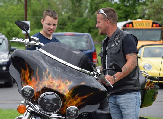 Grant Norris, a Forest Rose School student, checks out a motorcycle with a member of the Missing Link MC, from Columbus.