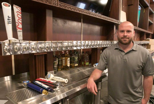 Drew Hagedon, general manager of Jameson's Irish Pub and Grill, poses Friday, May 24, 2019 in front of the 72 taps the restaurant and bar's new location in Brighton will offer.