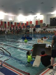 "Pinckney High School students row their homemade cardboard boats in the pool at Pathfinder School as part of the 22nd annual ""Pirate Regatta""."
