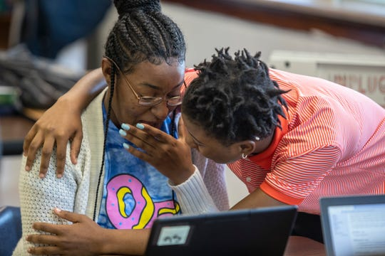 Shawnee High School student De'Nasha Turner, left, is congratulated by a classmate after getting news that she is the recipient of college scholarship from JCPS. May 24, 2019.
