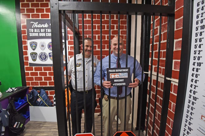 Assistant Mansfield police chief Joseph Petrycki and Mansfield police chief Keith Porch spend time behind bars after the opening of the police exhibit at the Little Buckeye Children's Museum.