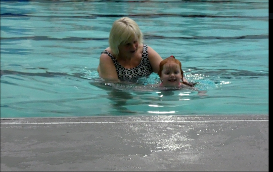 Karen Leedom, who has taught swimming lessons at the Friendly House for 40 years, Thursday night showcased her preschoolers' accomplishments at the annual preschool swim show. Averie Chillik smiles as she heads to the side of the pool.