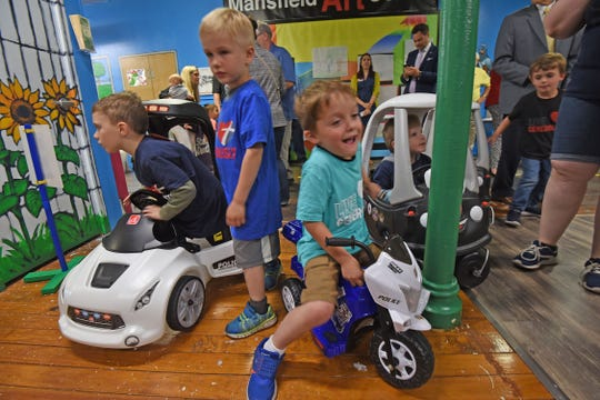 Children enjoy the vehicles at the Little Buckeye Children's Museum's police exhibit Wednesday after the ribbon cutting for the display.