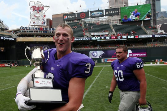 Wide receiver Tanner Vik walks on the field with the Holy Grail trophy after St. Thomas' victory over St. John's in a college football game in 2017. St. Thomas is looking for a new athletic conference and the WIAC could be a possibility.