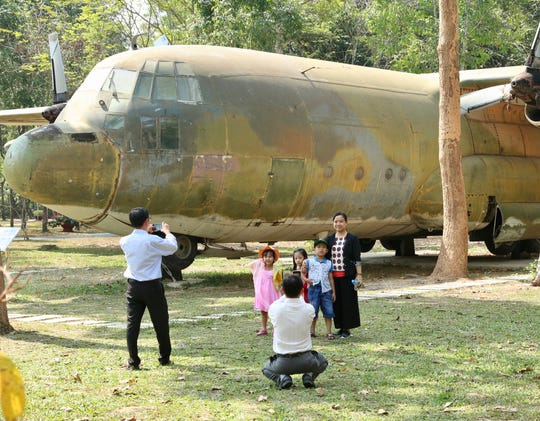 A family poses in front of a captured U.S. transport plane at the Cu Chi Tunnels.