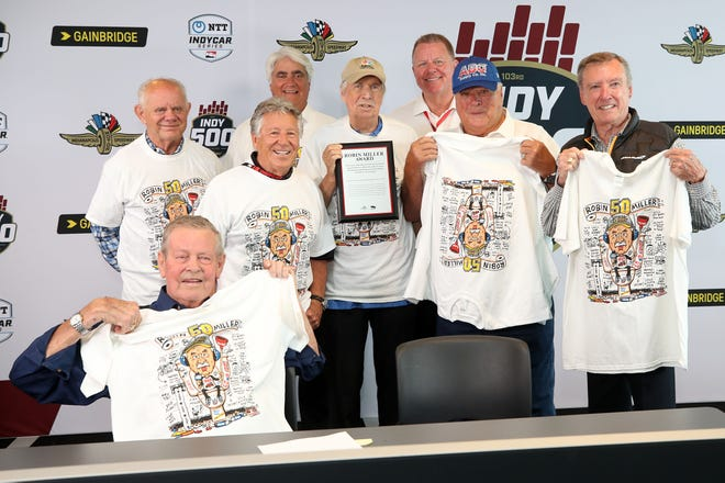Longtime Indianapolis motor sports reporter Robin Miller is surrounded by, from left, Paul Page, Bobby Unser, Mario Andretti, IndyCar President Jay Frye, Hulman & Company CEO Mark Miles, A.J. Foyt and Johnny Rutherford after a ceremony Friday at the Indianapolis Motor Speedway.