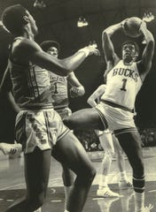 Oscar Robertson pulls down a rebound against Baltimore in 1971. He finished the Finals series averaging 23.5 points, 9.5 assists and five rebounds.