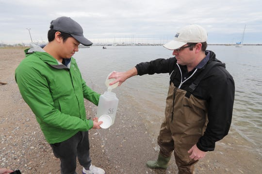 Lab technician Ame Xion (left) collects a water sample from Todd Miller before taking a measurement on May 24 at South Shore Park in Milwaukee. Miller is an associate professor at the University of Wisconsin-Milwaukee Zilber School Of Public Health. They were testing for E. coli, pharmaceuticals, personal care products, recreational drugs, and other pollutants.