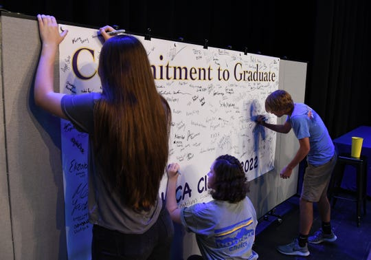 "Mountain Home freshmen sign a ""Commitment to Graduate"" banner Thursday afternoon in Dunbar Auditorium."