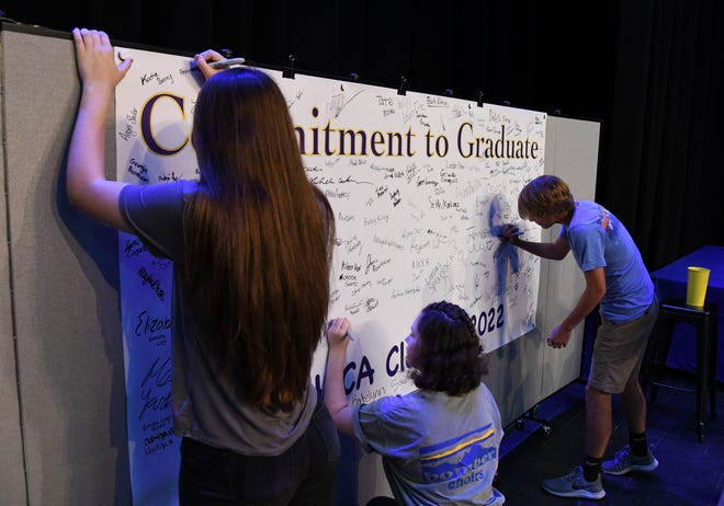 """Mountain Home freshmen sign a """"Commitment to Graduate"""" banner Thursday afternoon in Dunbar Auditorium."""