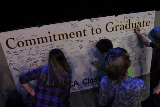 "Mountain Home freshmen sign the ""Commitment to Graduate"" banner on Thursday. This year's freshmen will graduate in 2022."