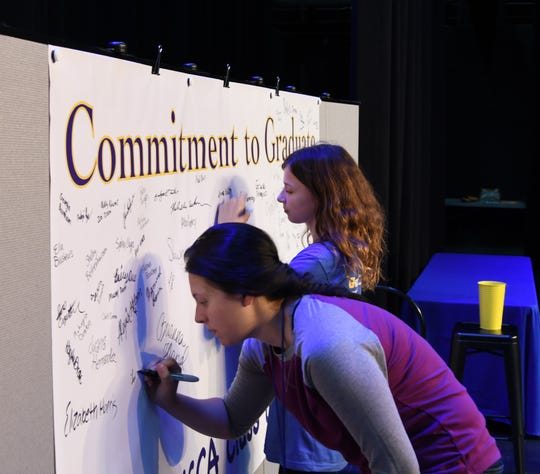 "Mountain Home freshmen sign the ""Commitment to Graduate"" banner. More than 300 students signed the banner during an awards ceremony Thursday."