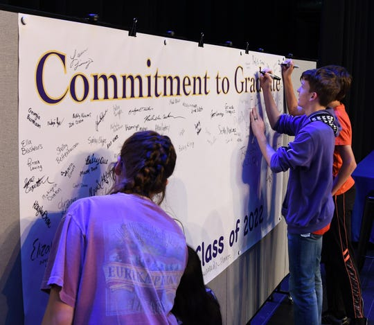 "Mountain Home freshmen add their names to the ""Commitment to Graduate"" banner Thursday afternoon."