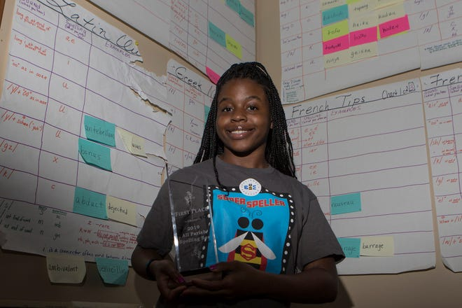 """Bre'Ann Washington, 14, stands for a portrait holding her All Parish Spelling Bee trophy against the backdrop of her 'rules and tips' charts, which she has been using since 2014, in her home in Monroe, La. on May 24. Washington is heading to Washington D.C. to compete in the Scripp's National Spelling Bee  this weekend. """"I feel excited, but it's also nerve wracking since I don't know what's ahead of me in the future,"""" Washington said. """"But, I know I'll do great things"""""""