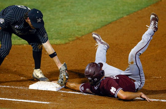 Mississippi State's Marshall Gilbert (34) keeps a hand on first base as he tries to avoid being picked off by Vanderbilt first baseman Julian Infante during the third inning of a Southeastern Conference tournament NCAA college baseball game Thursday, May 23, 2019, in Hoover, Ala.