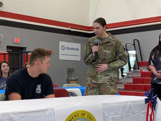 U.S. Army recruit William Lewis (left) listens to his sister, Private First Class Sarah Lewis as she speaks at Johnstown-Monroe High School's first Military Commitment Ceremony on Friday, May 24, 2019. Lewis said her brother's patriotism inspired her to enlist.