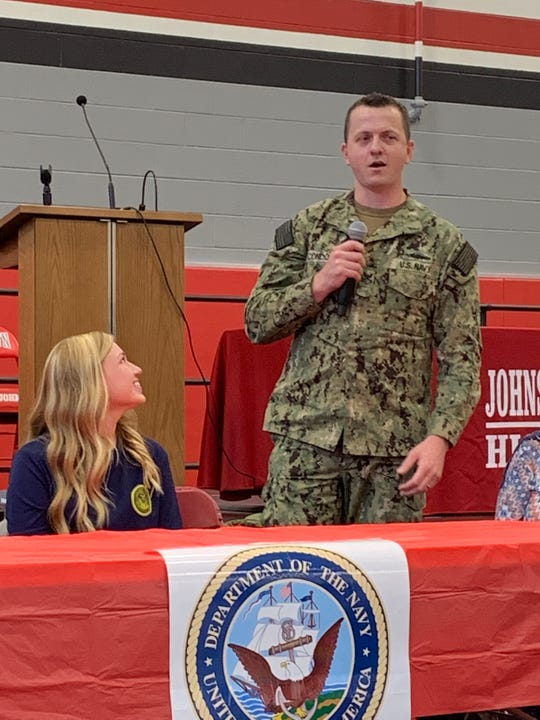 U.S. Navy recruit Hailey Peterman smiles at Petty Ofc. James Conden as he speaks about her at Johnstown-Monroe High School's first Military Commitment Ceremony on Friday, May 24, 2019.
