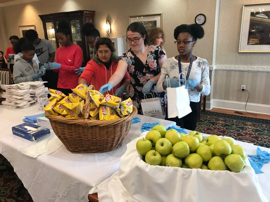 Kindness Hour in Hackensack, NJ. Students add chips and yummy green apples to lunches for homeless in Newark.