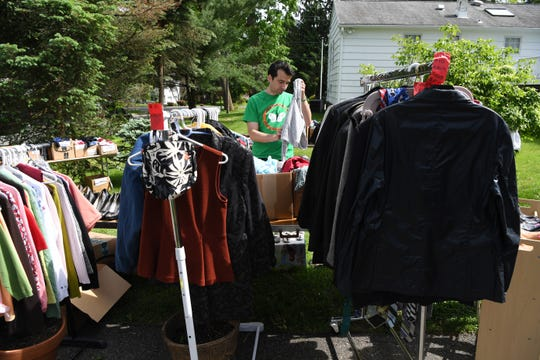 Rosemarie D'Alessandro holds her annual garage sale to benefit Joan's Joy, the foundation she set up as a legacy to her murdered 7-year-old daughter. Rosemarie D'Alessandro's son John D'Alessandro folds clothes during the garage sale on Friday, May 24, 2019.
