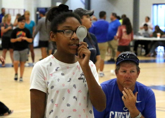 Tuynisha Green, 12, takes the eye exam on Thursday evening at the Carlsbad High gymnasium. CHS provided free physicals to all students in preparation for the upcoming school year.