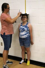 Valorie Vidrine, 12, gets her height measured on Thursday evening at the Carlsbad High gymnasium. CHS provided free physicals to all students in preparation for the upcoming school year.