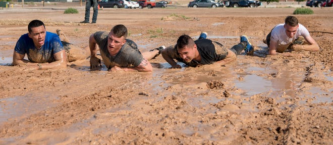 Fire Team Alpha crawls through the final phase of the mud crawl challenge, May 16, 2019, on Holloman Air Force Base, N.M. The challenge was in place to demonstrate and refine the skills of security forces Airmen during Police Week.
