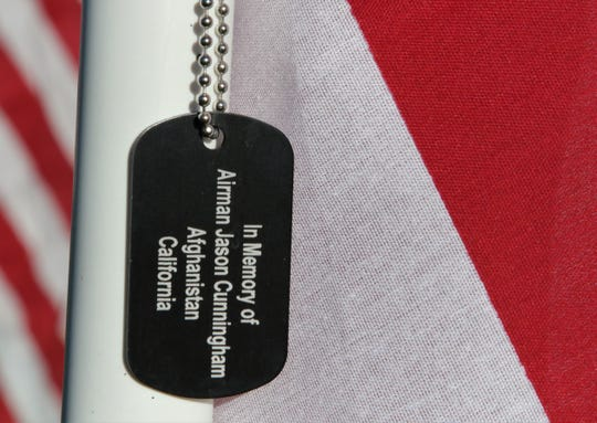 A dog tag hanging on a flag in the Healing Field memorializes Jason Cunningham, an airman from California who was killed in 2002 in action in Afghanistan.
