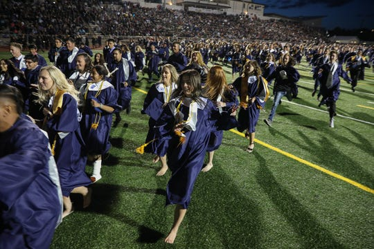 Piedra Vista's Class of 2019 run to the end of the football field in celebration at the conclusion of the commencement exercises on Thursday at the Hutchison Stadium.