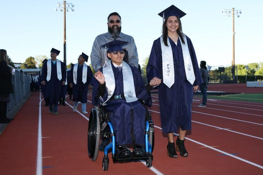 Piedra Vista graduate Jesse Armenta is pushed by his father Edward Armenta while walking with cousin Alysa Acosta during processional march on Tuesday at the Hutchison Stadium. SPECIAL TO THE DAILY TIMES - CURTIS RAY BENALLY