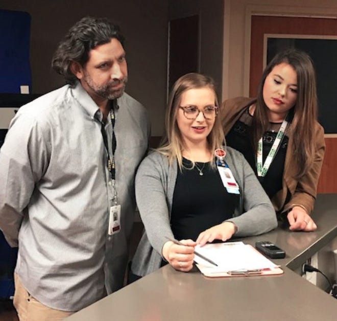 Laura Condit, center, lead behavioral health social worker at St. Mary Mercy Livonia, consults with Growth Works peer recovery coaches Sean Davis, left, and Sarah Spencer, right, in the hospital's emergency room.