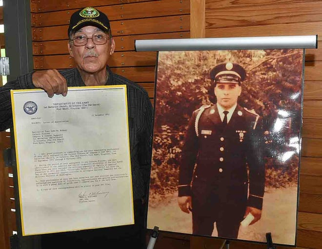 John Rideau, next to a picture of himself in uniform in the early 1970s.