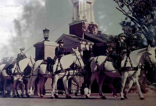 John Rideau, on the center horse, helps transport a veteran's casket to the Arlington National Cemetery during the Vietnam War.