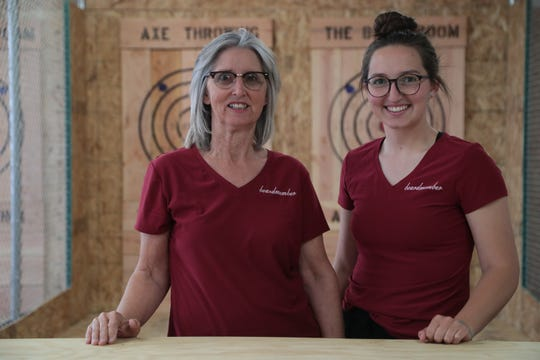 Audry Wilcox, right, helps out her mother Bridget in the first days of the opening of their new ax throwing business in Twentynine Palms, Calif., May 22, 2019.