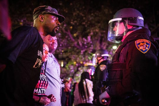 A Black Lives Matter protester stares at a California Highway Patrol officer during a protest in Sacramento following the police shooting of Stephon Clark. California lawmakers have struck a deal that will impose the nation's highest standards for use of police force on the state.