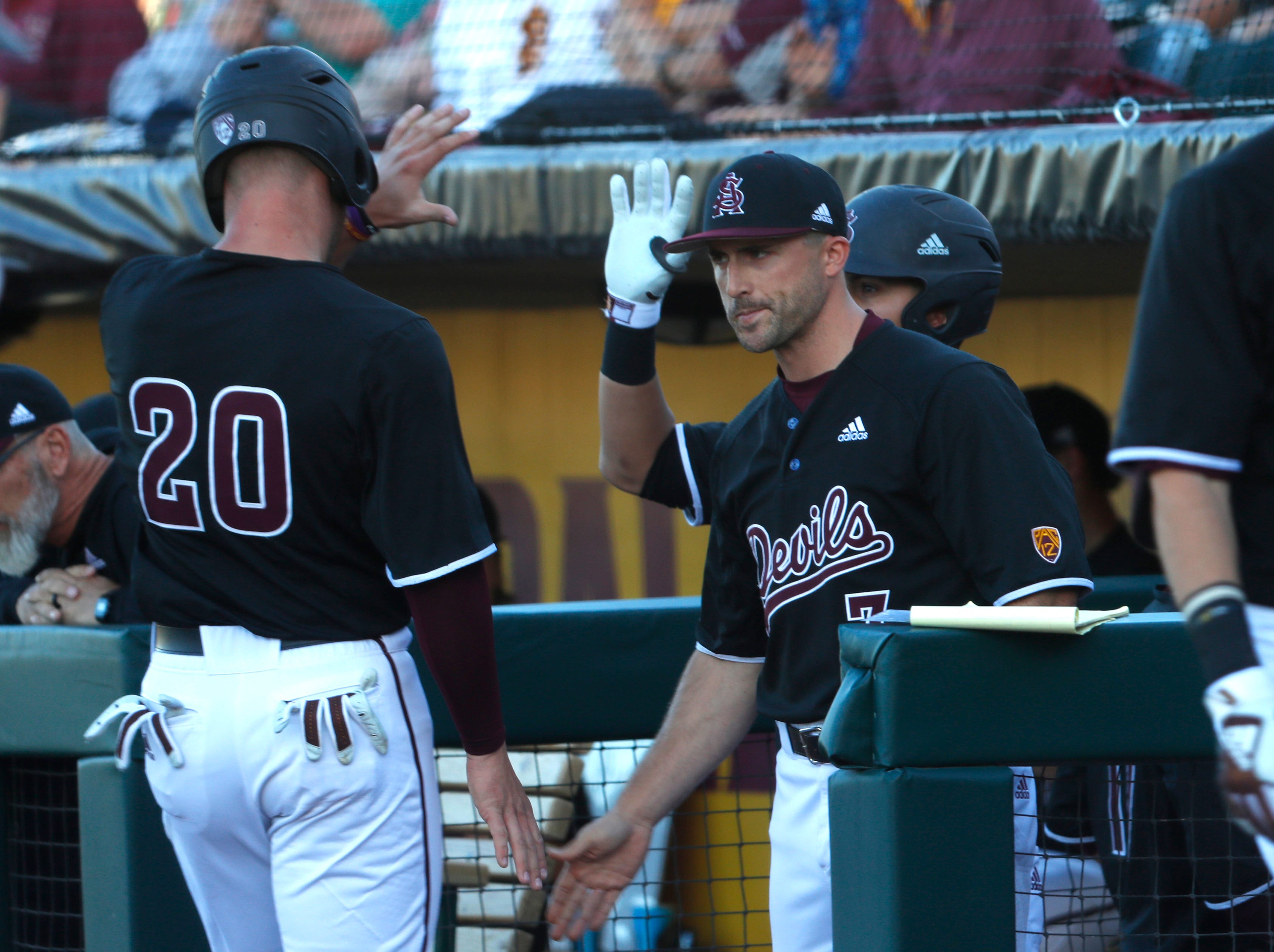 ASU's hitting coach Michael Early (R) high-fives Spencer Torkelson (20) after Torkelson scored in the first inning against Stanford at Phoenix Municipal Stadium in Phoenix, Ariz. on May 23, 2019.