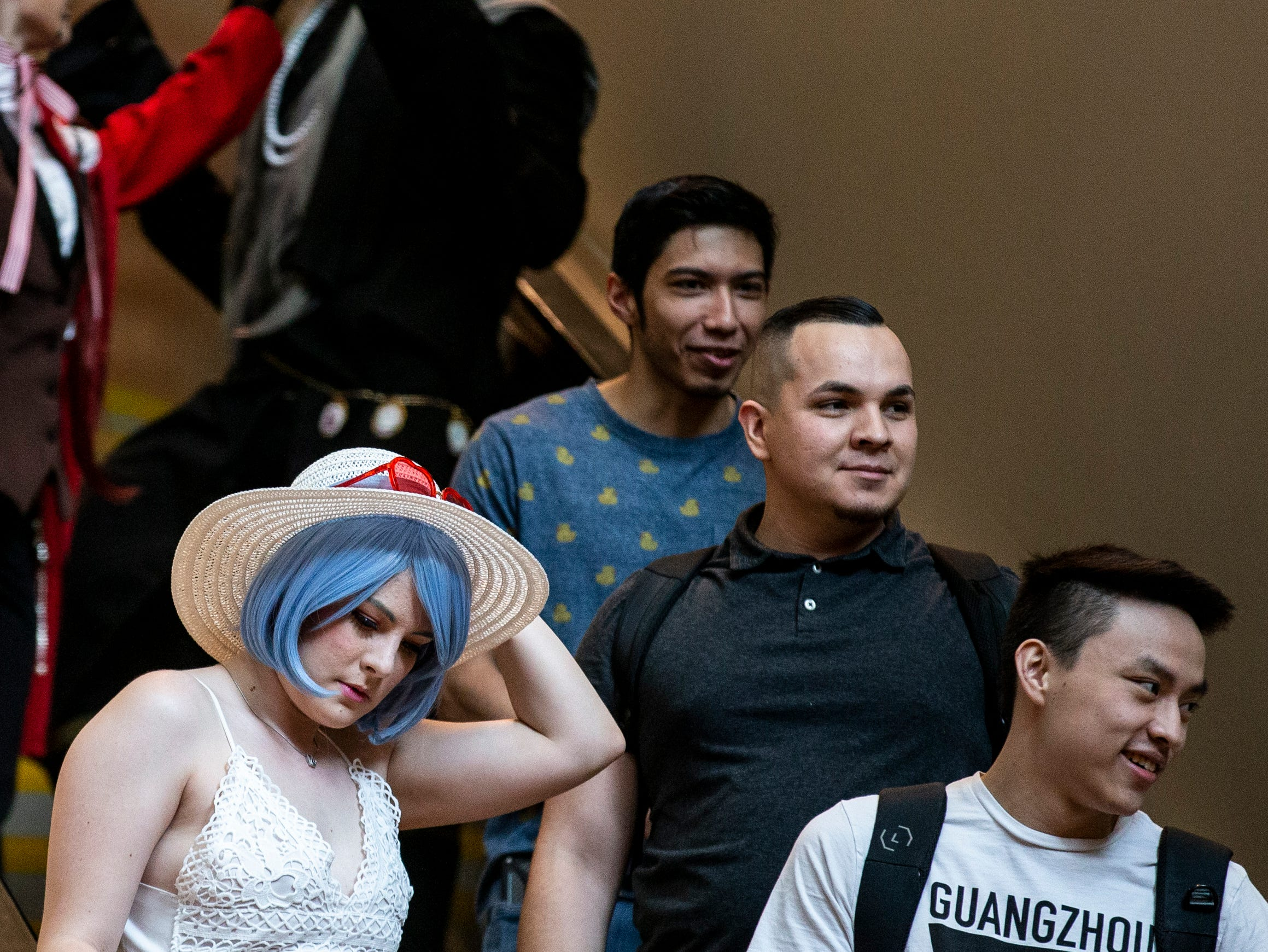 Attendees ride down an escalator during Day 1 of Phoenix Fan Fusion on Thursday, May 23, 2019, at the Phoenix Convention Center in Phoenix.