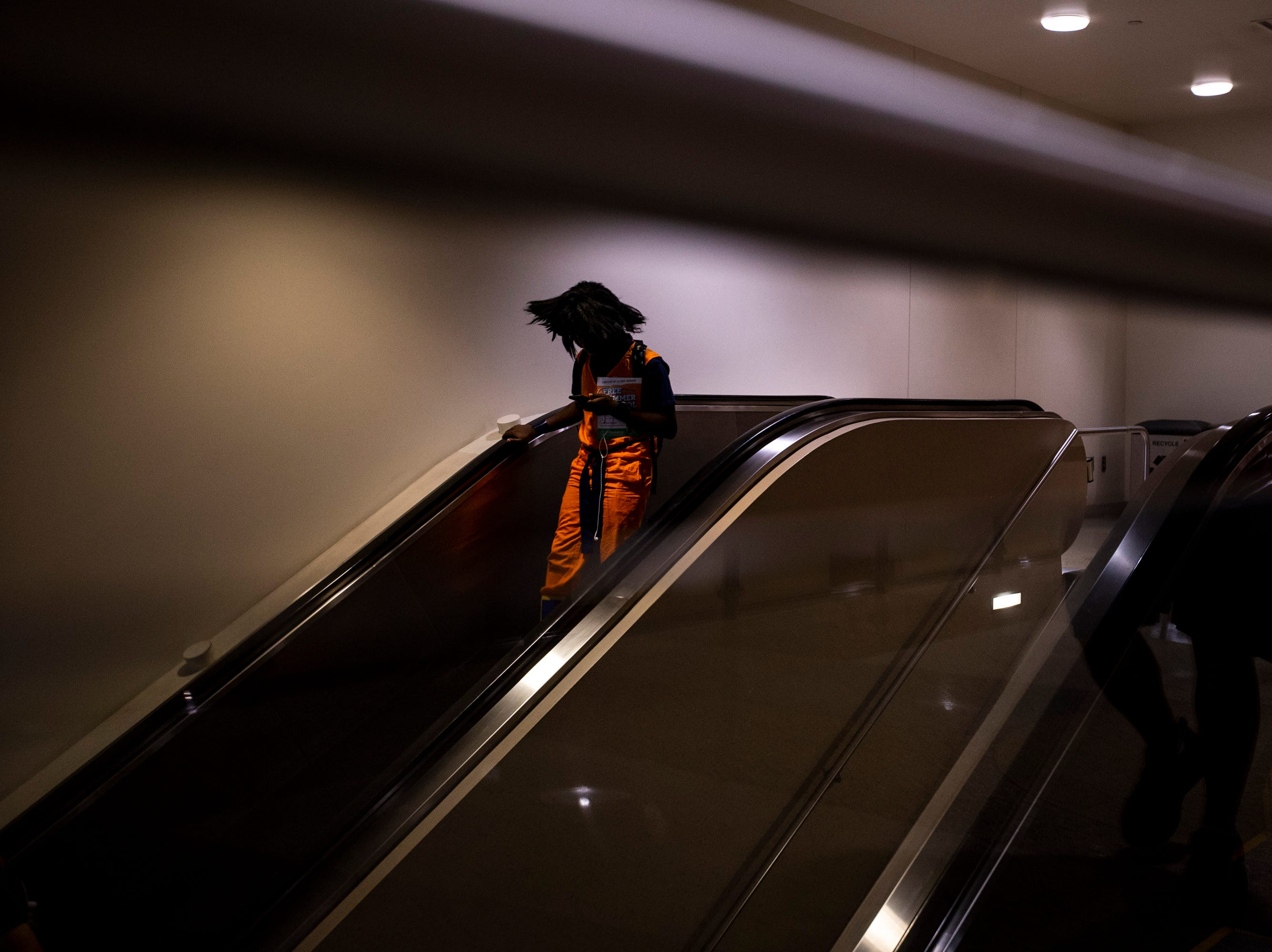 An attendee rides down an escalator during Day 1 of Phoenix Fan Fusion on May 23, 2019, at the Phoenix Convention Center in Phoenix.